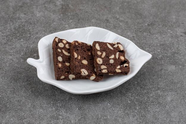 Fette di torta al cioccolato su piatto bianco su superficie grigia