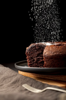 Chocolate cake sprinkled with sugar powder on a black plate