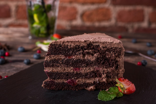 Chocolate cake on a stone plate on rustic wood table