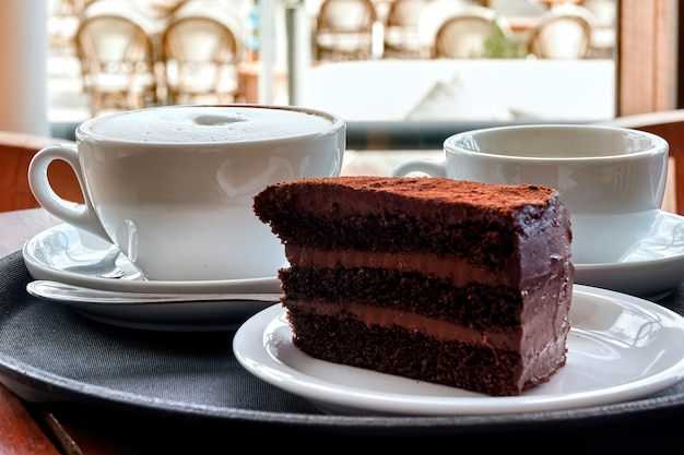 Chocolate cake and two cups of coffee