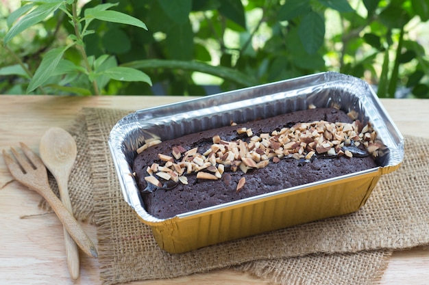 Chocolate cake with almond topping in aluminum foil box packaging.
