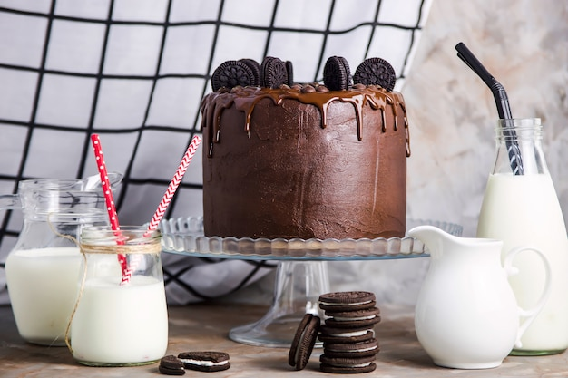 Chocolate cake with biscuits on a glass stand among the vessels with milk