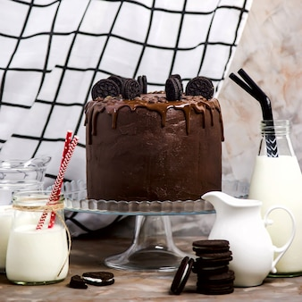 Chocolate cake with biscuits on a glass stand among the vessels