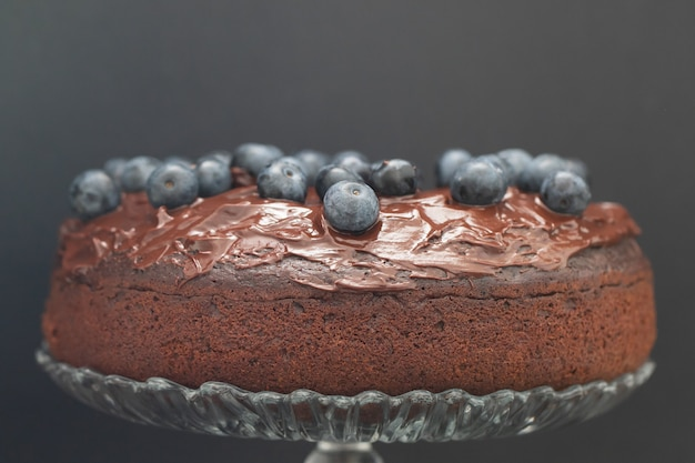 Chocolate cake with blueberries on black surface