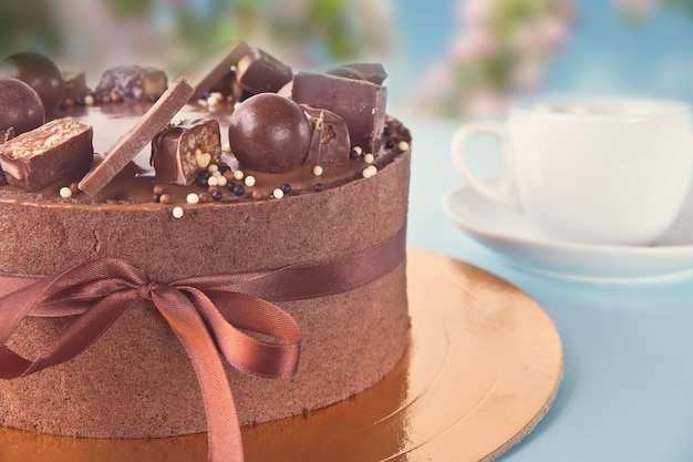 Chocolate cake with candy and ribbon on a blue table