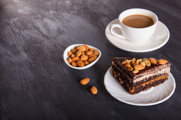Chocolate cake with caramel, peanuts and almonds on a black wooden background.
