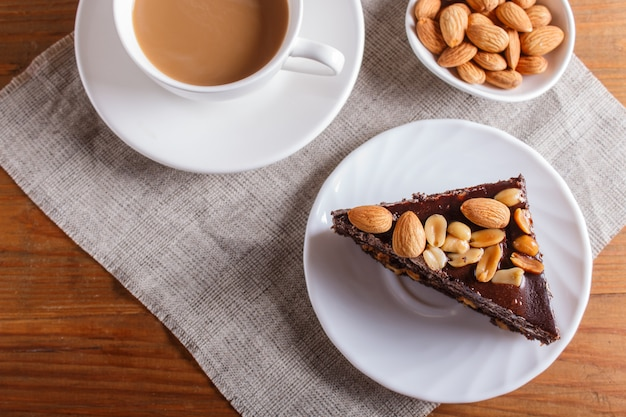 Chocolate cake with caramel, peanuts and almonds on a brown wooden background.