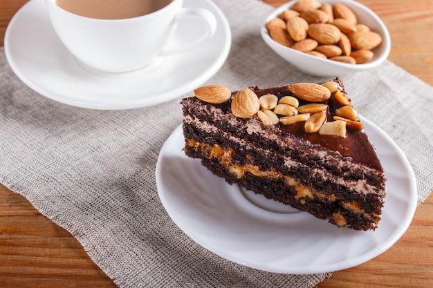 Chocolate cake with caramel, peanuts and almonds on a brown wooden surface.