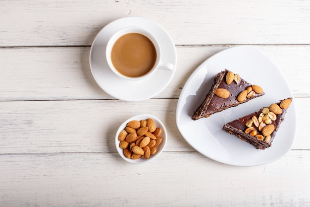Chocolate cake with caramel, peanuts and almonds on a white wooden background.