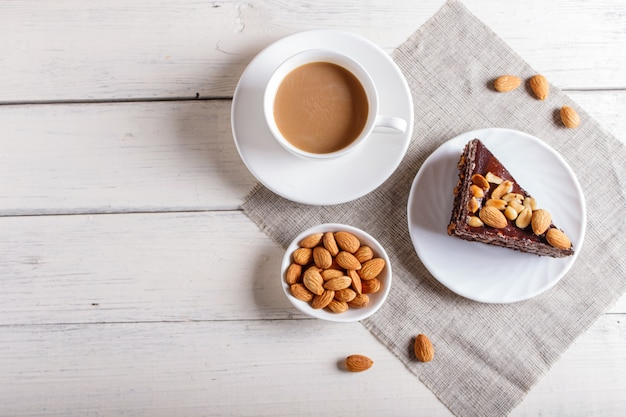 Chocolate cake with caramel peanuts and almonds on a white wooden background