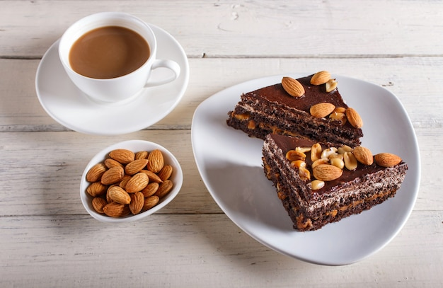 Chocolate cake with caramel, peanuts and almonds on a white wooden surface.