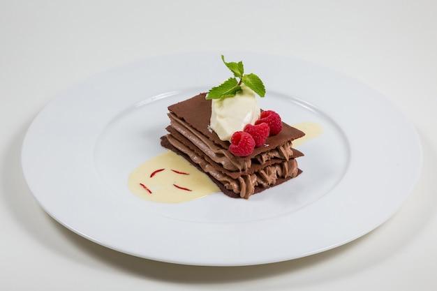 巧克力蛋糕与巧克力奶油美丽地放置在一个白色地方