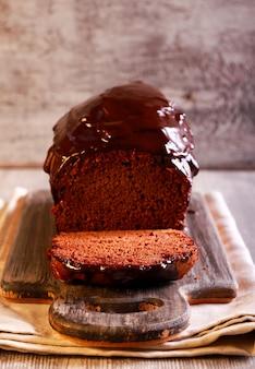 Chocolate cake with chocolate icing on board, sliced