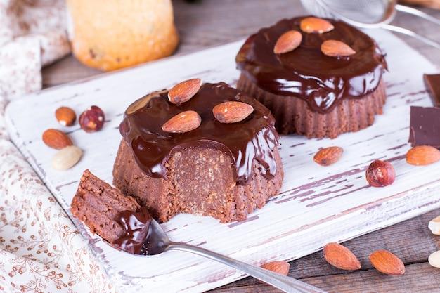 木製のテーブルにチョコレートのアイシングとチョコレートケーキ