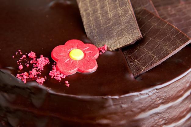 초콜릿 장식품과 붉은 마지판 장미가 있는 초콜릿 케이크. 초콜릿 케이크 마지판 장식