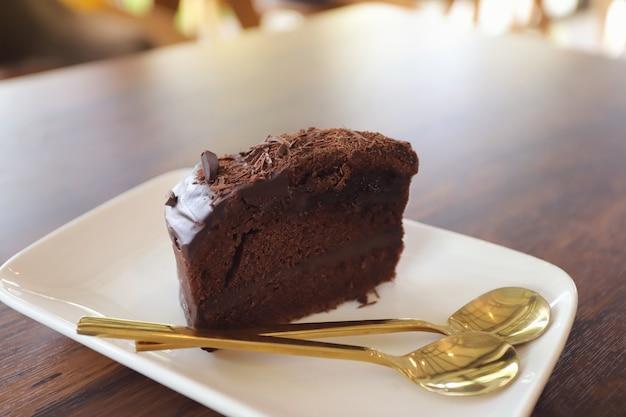 Шоколадный торт с шоколадной начинкой в белом блюде на деревянном столе