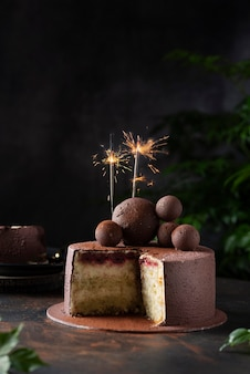 Chocolate cake with christmas sparklers on a dark backgroud, selective focus image