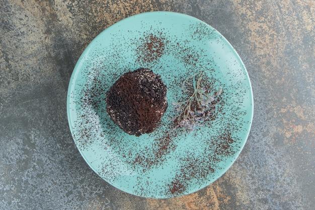 Una torta al cioccolato con cacao in polvere su un piatto blu