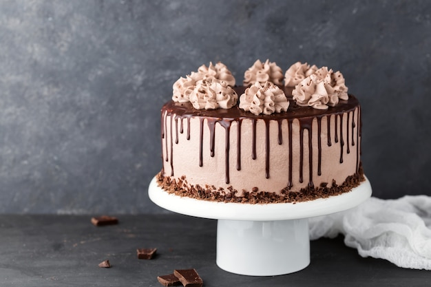 Chocolate cake with coffee cheese cream on a white cake stand