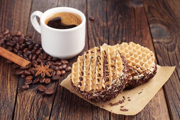 暗い木製のテーブルにクリームとホットコーヒーのカップとチョコレートケーキ