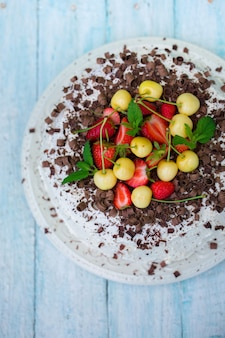 신선한 딸기와 노란 체리를 곁들인 초콜릿 케이크