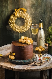 Chocolate cake with gold decor champagne behind rustic style high quality photo