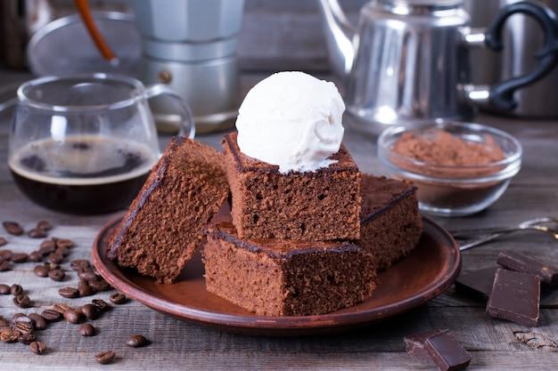 木製のテーブルの上のプレートにアイスクリームとチョコレートソースとチョコレートケーキ