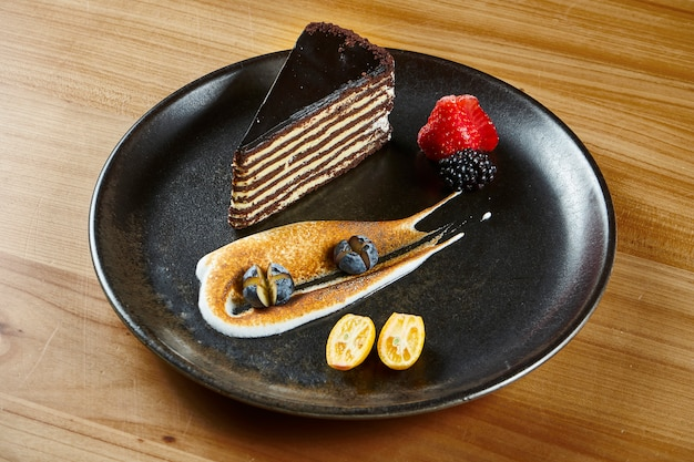 Chocolate cake with layers and pastry cream on wooden surface