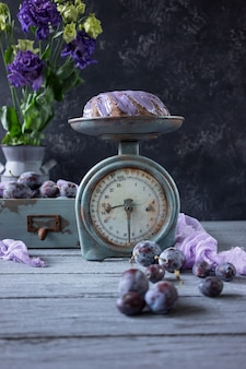 Chocolate cake with lilac flowers and plums in a vintage wooden box