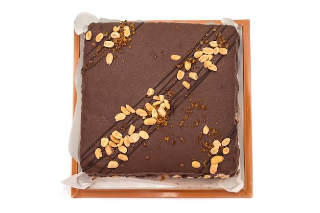 白で隔離の段ボール箱にナッツとキャラメルのチョコレートケーキ。