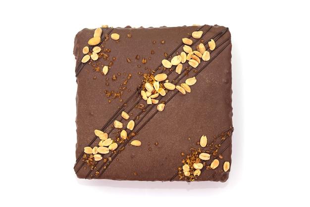 白に分離されたナッツとキャラメルのチョコレートケーキ。
