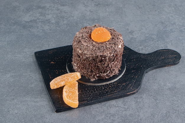 Torta al cioccolato con caramelle di gelatina d'arancia su una tavola scura