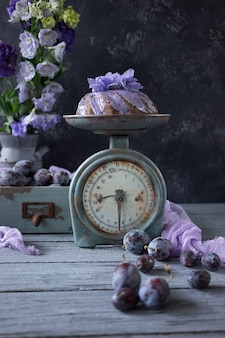 Chocolate cake with plums and lilac flowers