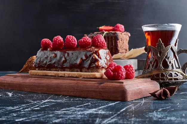 Шоколадный торт с малиной и стаканом чая.