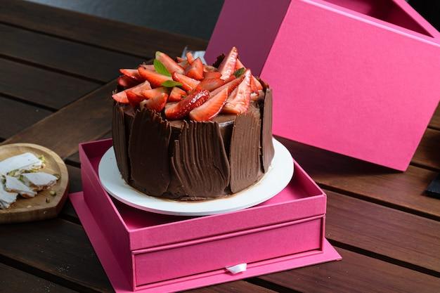 ピンクの箱にイチゴ、バジルの葉、チョコレートプレートが入ったチョコレートケーキ。トゥロンの隣。