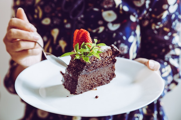 Chocolate cake with strawberry fruit topping on white plate in woman's hand.