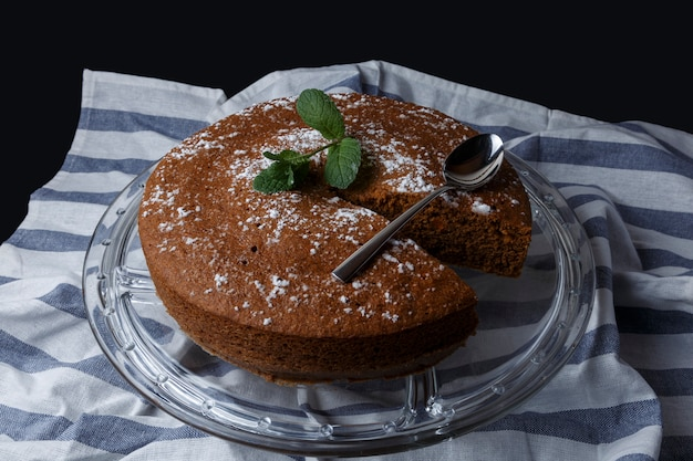 Chocolate cake with sugar decoration on glass stand