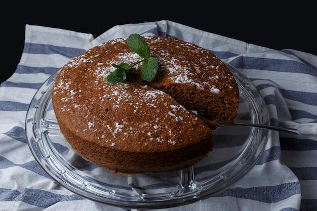 ガラススタンドに砂糖の装飾が施されたチョコレートケーキ