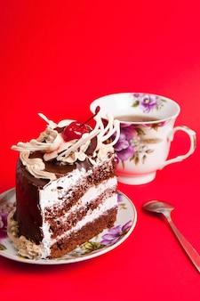 赤い背景にお茶とチョコレートケーキ
