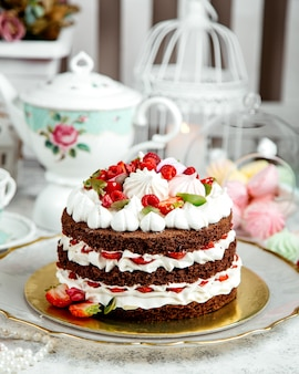 Chocolate cake with whipped cream and fruits