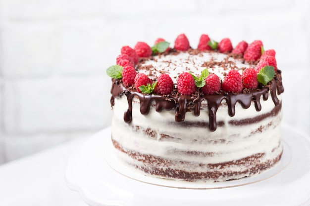 Chocolate cake with white cheese cream decorated ganache and raspberries on a white cake stand, copy space