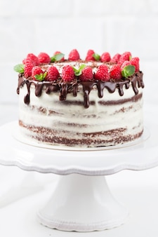 Chocolate cake with white cheese cream decorated ganache and raspberries on a white cake stand