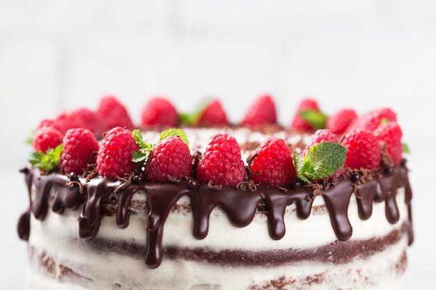 Chocolate cake with white cheese cream decorated ganache and raspberries