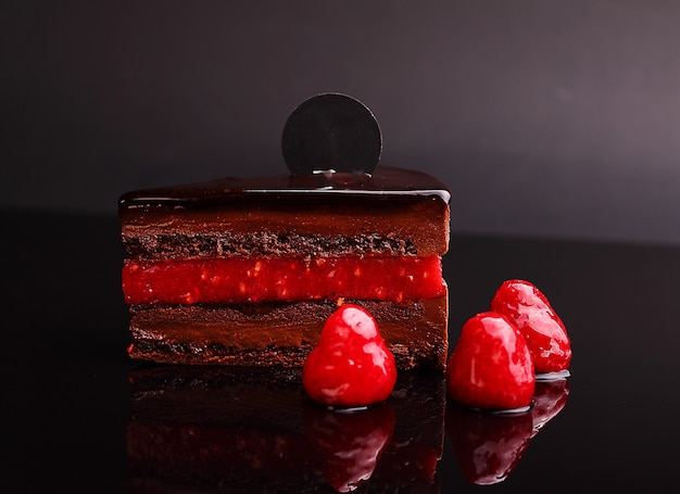 Chocolate cake zacher with raspberry, mousse in the mirror reflection, section. on the black background.