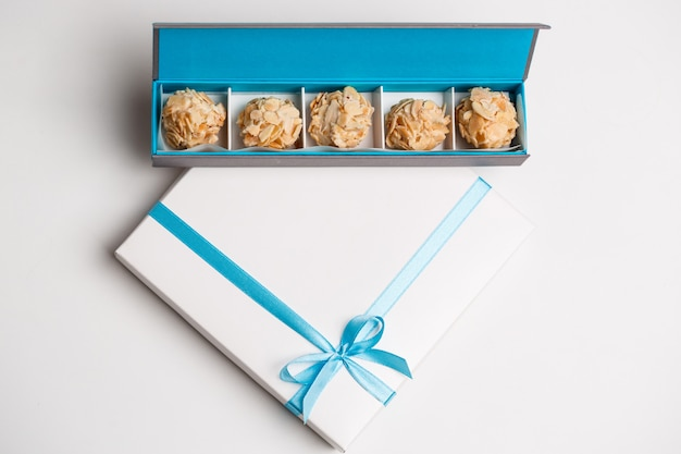 Chocolate candies in box on white