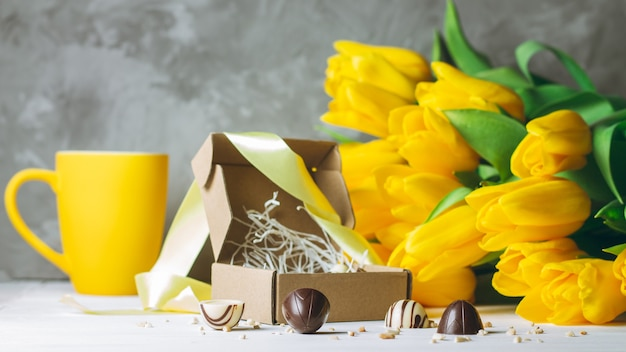 Chocolate candies in craft box, cup and bouquet of yellow tulips on white wooden surface on gray surface