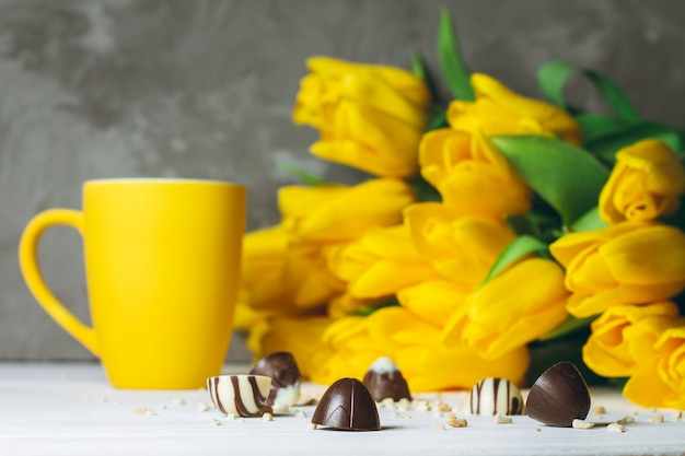Chocolate candies, cup and bouquet of yellow tulips on white wooden surface on gray surface