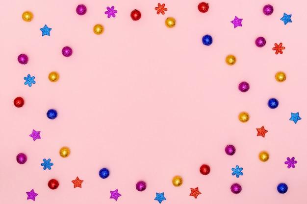 Шоколадные конфеты, декоративные звезды и снежинки на розовой бумаге