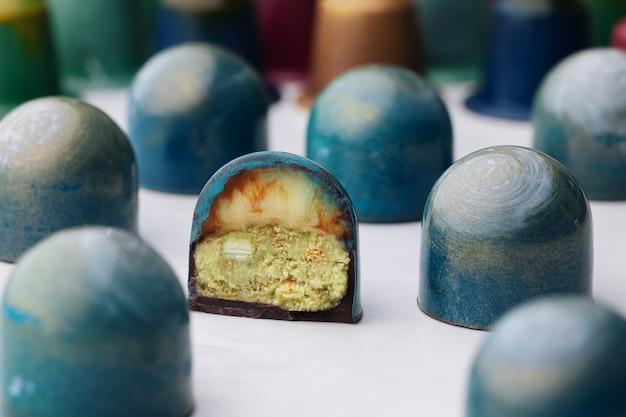 Шоколадные конфеты куполообразной формы с кремом амаретто и фисташковой вафельной крошкой ганаш