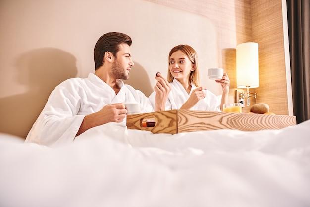 朝食用のチョコレート菓子。カップルはホテルの部屋のベッドで一緒に食事をしています。ラブストーリー。白いベッドの上のチョコレート